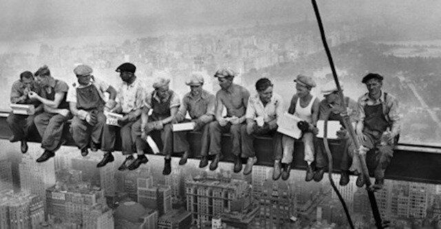 Budowniczowie spokojnie jedzą obiad, siedząc na belce na wysokości 200 metrów nad ziemią